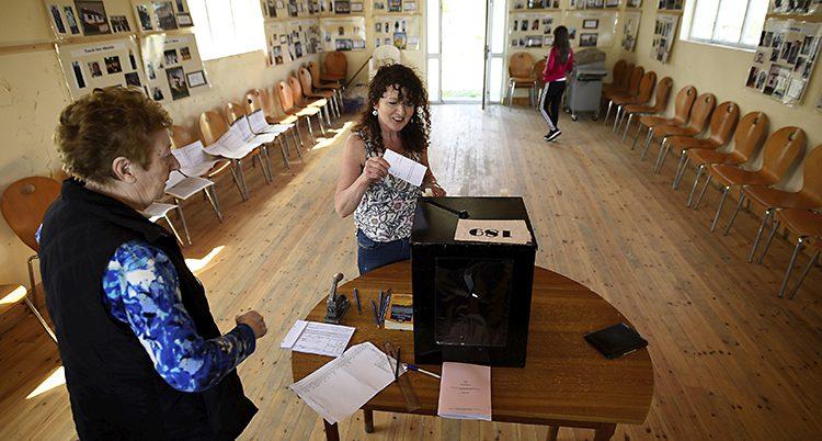 En kvinna lägger sin röst i en låda.