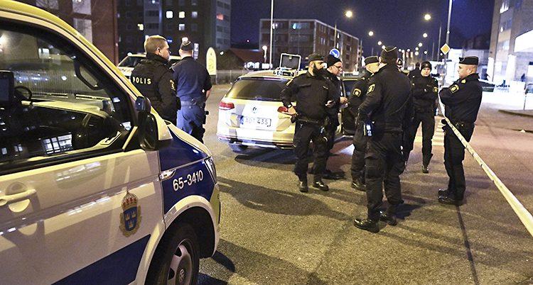 Poliser samlade vid en polisbil en kväll