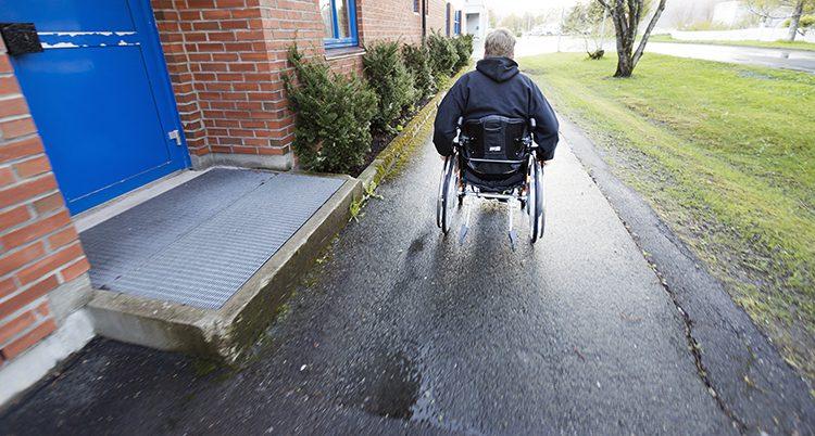 En bild på en man i rullstol bakifrån.