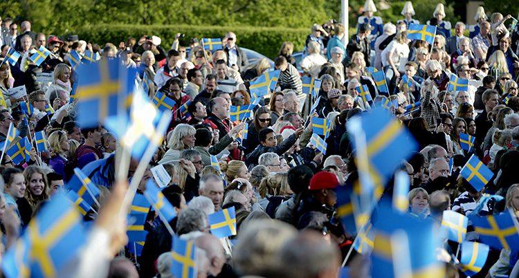 Folk viftar med flaggor på Skansen på nationaldagen.