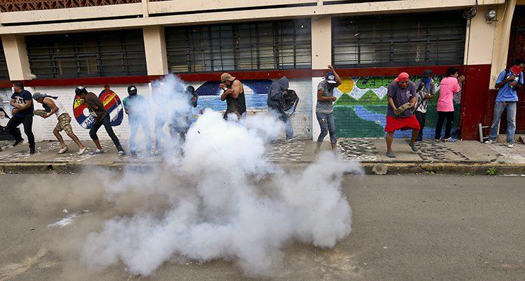 Människor på en gata skyddar sig mot tårgas.