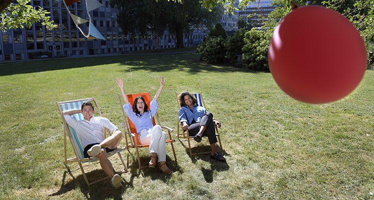 Tre programledare sitter i solstolar på en gräsmatta.