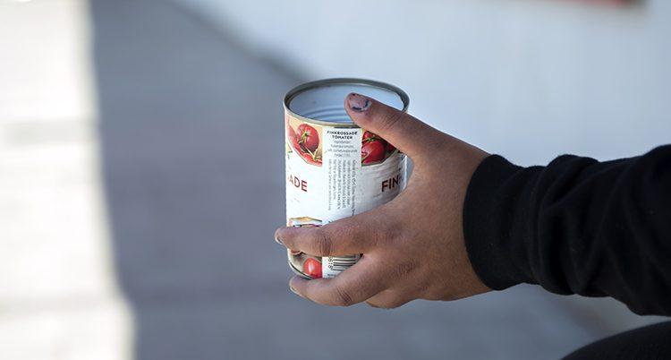 En hand som håller en tom konservburk.