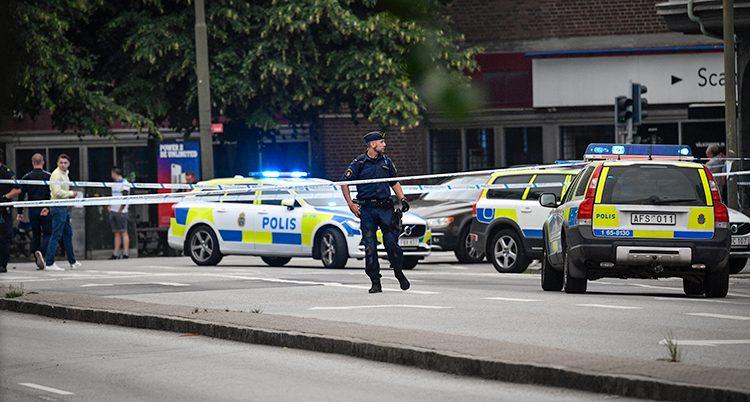 Flera polisbilar och en polis syns bakom en avspärrning.