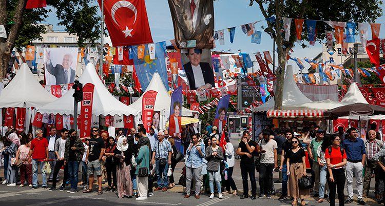 Folk på en gata i Istanbul. Gatan är fylld med tält och flaggor inför valet.