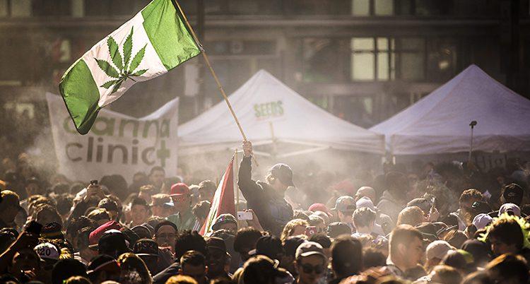 En stor folksamling. En av människorna viftar en flagga med ett cannabisblad på.