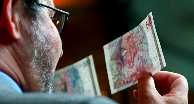 En man tittar på gamla sedlar.