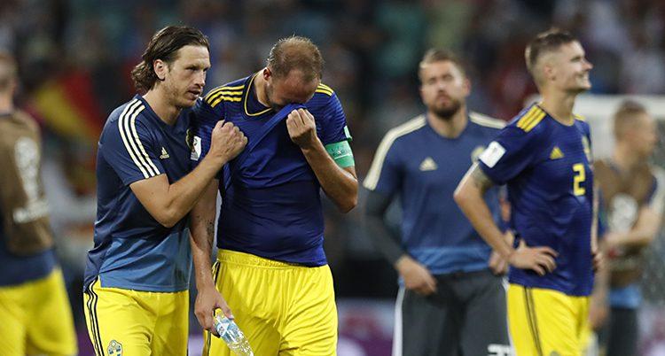 Ledsna svenska spelare på en fotbollsplan.