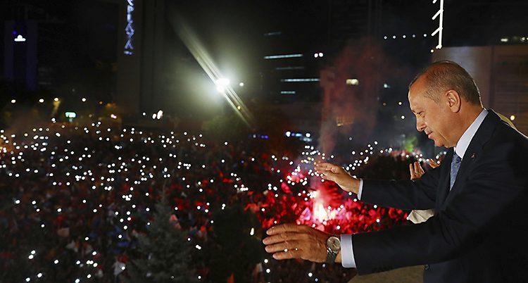 Turkiets president Erdogan står på en balkong och vinkar till människor nedanför.