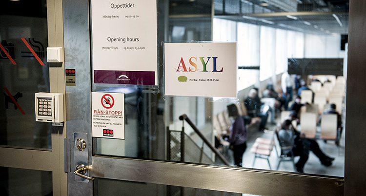 Skylt på en glasdörr där det står Asyl. Innanför väntar människor sittande på stolar.