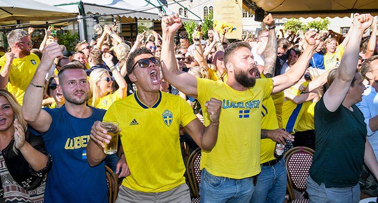 Människor i landslagets gula tröja skriker av glädje.
