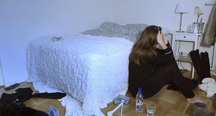 En ledsen flicka sitter på golvet bredvid sin säng.