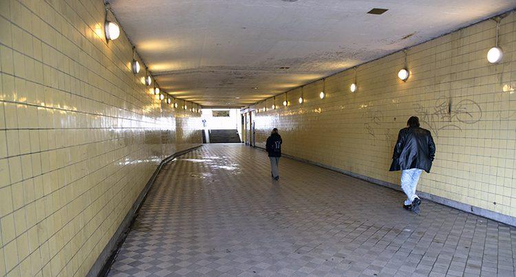 Några personer går genom en lång tunnel i Stockholm.