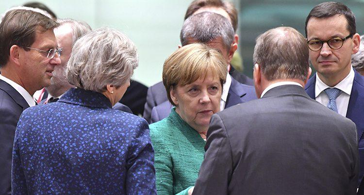 Angela Merkel står och pratar med Theresa May och Stefan Löfven.