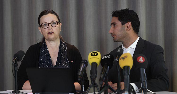 Anna Ekström och Ardalan Shekarabi står framför flera mikrofoner.