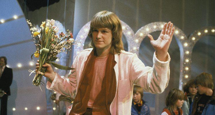 Ted Gärdestad på Melodifestivalen 1979. Han vinkar till publiken med en bukett i handen. Han har just vunnit med sin låt Satellit.