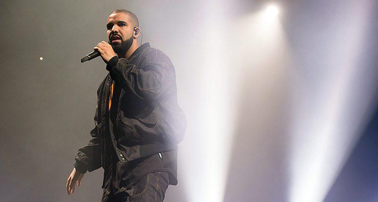 Rapparen Drake uppträder. Han har en svart bomberjacka och svarta byxor. Två strålkastare lyser med ett vitt ljus nedifrån och upp på scenen.