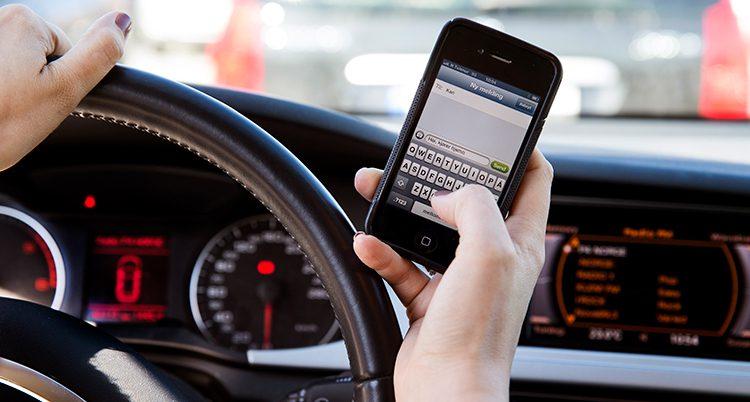 En person sitter i en bil. Vi ser över axeln på personen som håller en hand på ratten och andra på sin mobil.