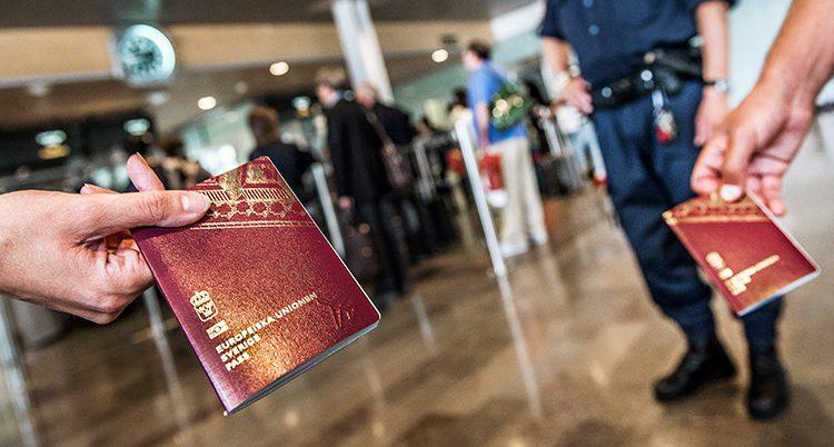 Två händer håller fram varsitt pass på en flygplats. I bakgrunden ses en uniformerad polis.