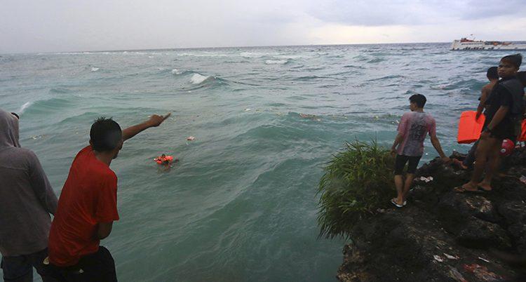 Folk står på en bergsklippa och tittar ut över havet och båten en bit bort. Någon håller en flytväst i handen. I havet ligger en person i flytväst, längre bort ser man människor kvar på båten.