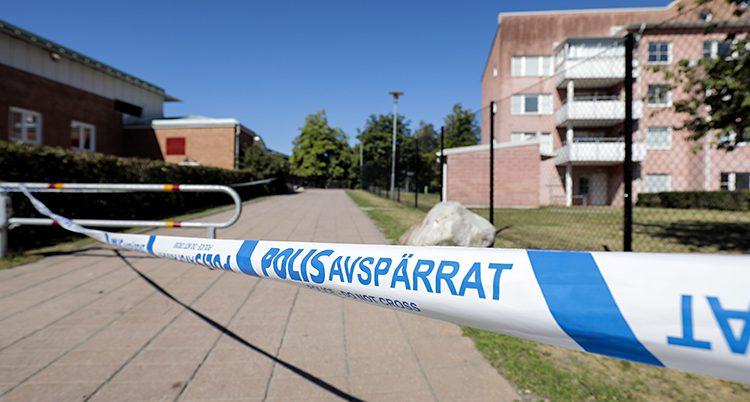 En gata vid ett bostadsområde är avspärrad av polisband.