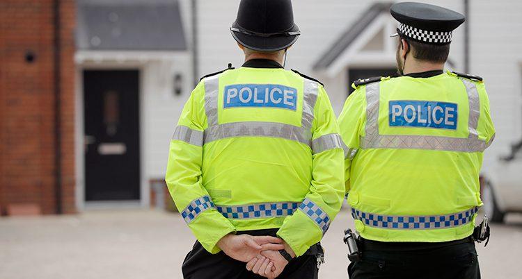 Två brittiska poliser med ryggen mot kameran.