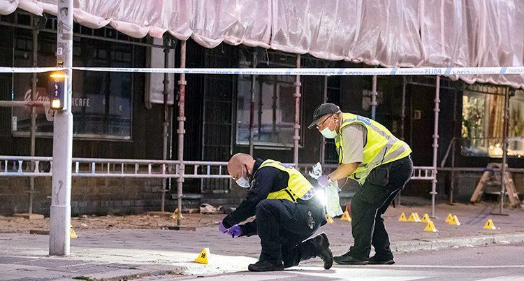 Tekniker från polisen undersöker bevis på en gata i Malmö.
