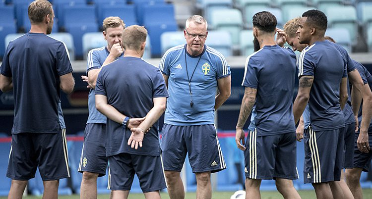 Janne Andersson har samlat spelarna på träning. Alla har blå träningskläder.