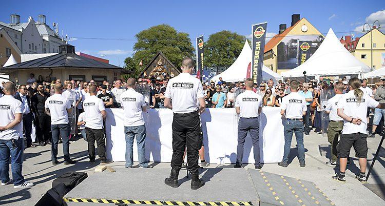 En rad män med ryggarna mot kameran står framför en folkmassa. Männen har likadana vita skjortor på sig.