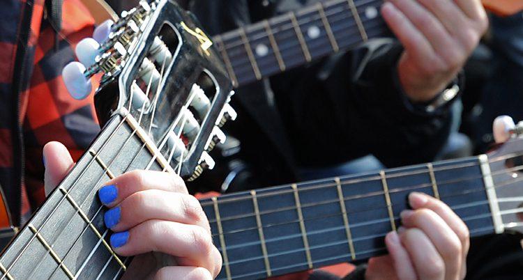 Folk som spelar gitarr.