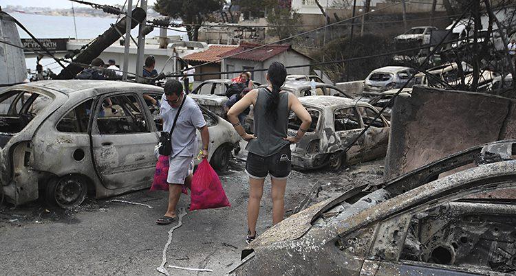 Folk går omkring bland brända bila