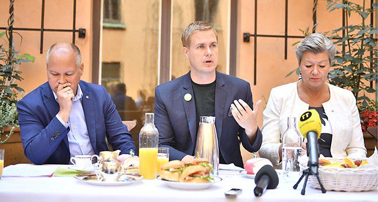 Tre ministrar sitter bredvid varandra vid ett uppdukat frukostbord.