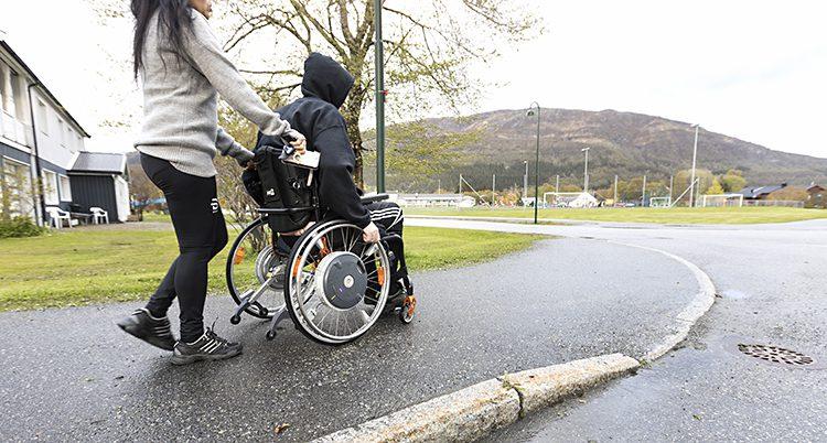 En gata utomhus. En person sitter i en rullstol. En annan person kör rullstolen. Vi ser dem bakifrån