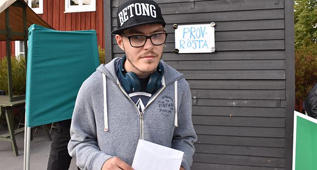 Douglas Falkenberg står utomhus med ett kuvert i handen.
