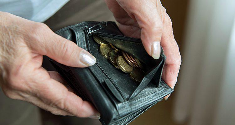 En person tittar på mynt i sin plånbok.