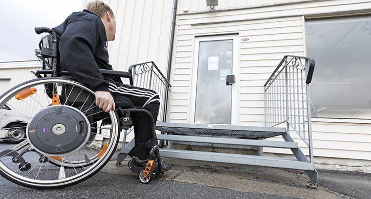 En person i rullstol framför ett hus med en trappa.