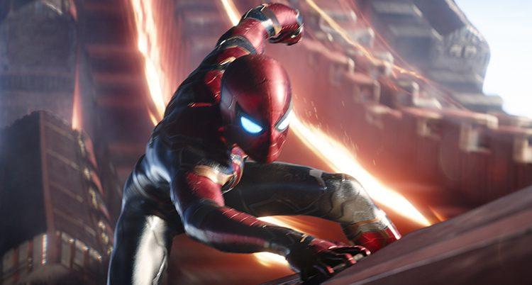 Spiderman klättrar och håller sig i med ena handen