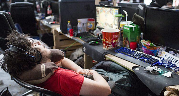 En ung kille sover framför datorn