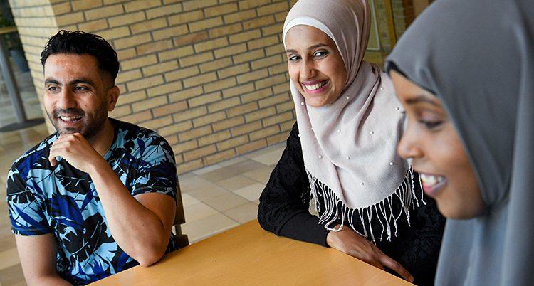 Tre personer sitter vid ett bord och skrattar.