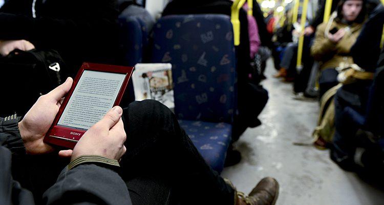 En man läser en e-bok i tunnelbanan