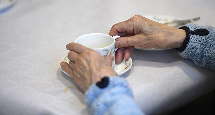Två händer håller i en kopp kaffe.