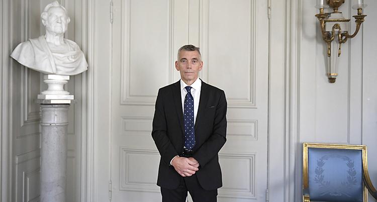 Eric M Runevall i kostym framför en vit vacker inomhusdörr.