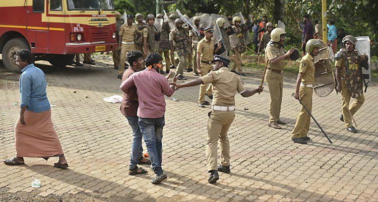En polis i bråk med män vid templet