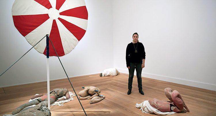 En person i mörka kläder står i ett hörn av ett ljust rum. På golvet ligger delar av kroppar som är gjorda av en konstnär.
