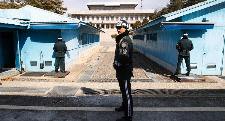 Några vakter står längs två låga blå byggnader.