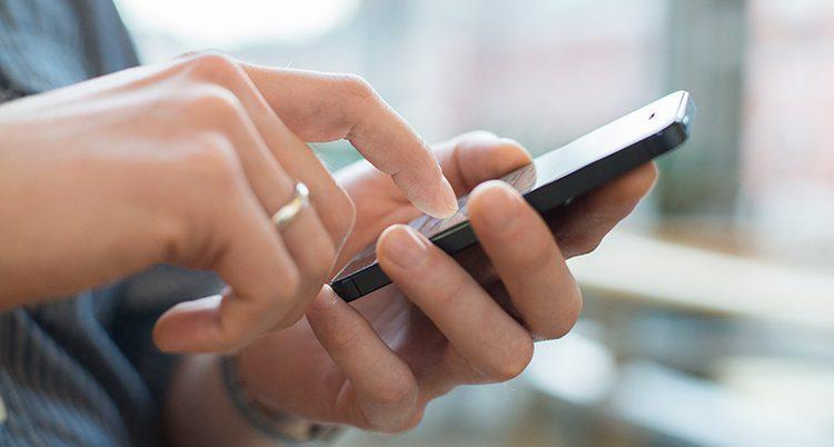 En hand som knappar på en mobiltelefon.