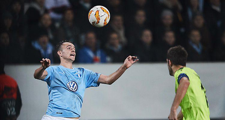 En fotboll i luften och två spelare.