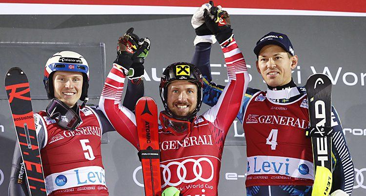 André Myhrer på prispallen tillsammans med ettan och tvåan i loppet. De håller varandra i händerna och höjer armarna i luften.