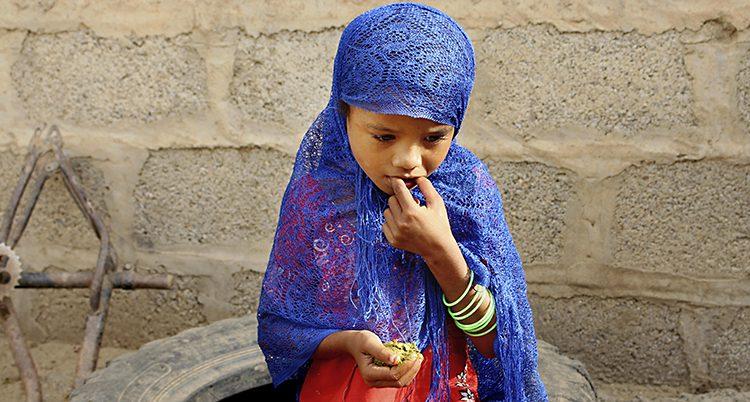 En flicka äter kokta löv.