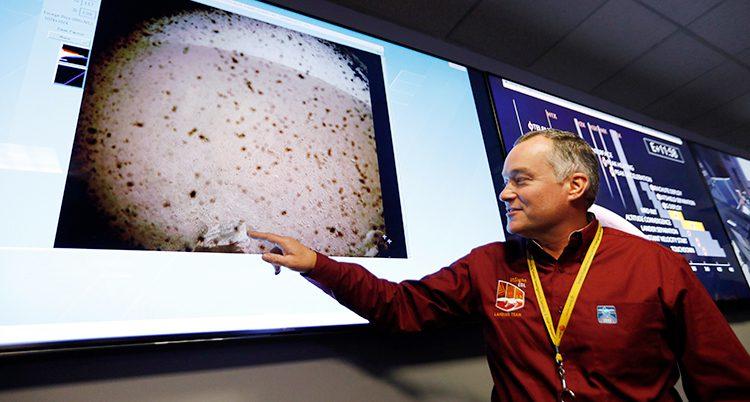 En man från rymdorganisationen Nasa pekar på de första bilderna från Mars.
